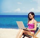 放松与在一个美丽的海滩的一台膝上型计算机的一个少妇 图库摄影