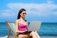 放松与在一个美丽的海滩的一台膝上型计算机的一个少妇 免版税库存照片