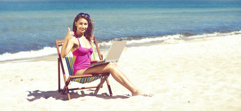 放松与在一个美丽的海滩的一台膝上型计算机的一个少妇 库存照片