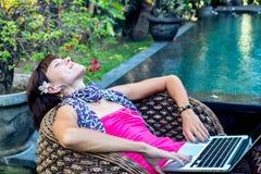 放松与在休息室的便携式计算机的性感的妇女在游泳池附近户外 巴厘岛热带庭院  免版税库存照片