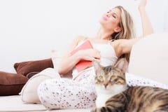 放松与在沙发的闭合的眼睛的美丽的愉快的年轻女人 免版税库存图片