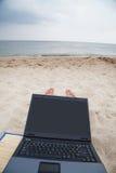 放松与在海滩的膝上型计算机 库存照片