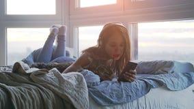 放松与她可爱的缅因树狸猫的耳机的年轻俏丽的妇女听到音乐唱歌曲放下在床上 股票视频