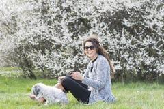 放松与她的白色狮子狗的美丽的妇女在春天庭院里 免版税库存照片