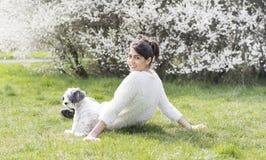 放松与她的白色狮子狗的美丽的妇女在春天庭院里 免版税库存图片