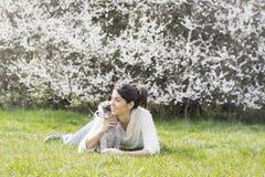 放松与她的白色狮子狗的美丽的妇女在春天庭院里 库存图片