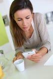 放松与智能手机和咖啡的妇女 免版税库存图片