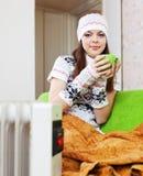 放松与杯子的妇女在加热器附近 免版税图库摄影