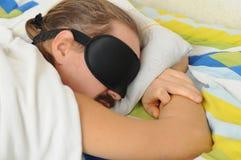 放松与睡眠面具的有胡子的年轻人在床上 免版税库存图片