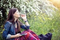 放松与耳机听到音乐的妇女坐草春天户外 库存照片