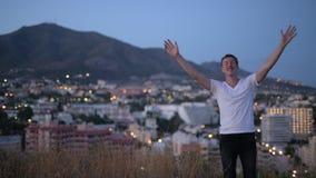 放松与胳膊的年轻愉快的旅游人被举在小山顶部在晚上 股票视频