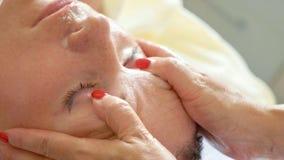 放松与面孔按摩的美丽的少妇在豪华温泉沙龙,特写镜头 库存图片