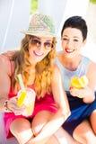 放松与饮料的湖海滩的两个朋友 免版税库存图片