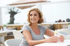 放松与水饮料的妇女在户外餐馆 库存图片
