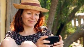 放松享用她的智能手机的妇女在庭院里在阳光下 影视素材