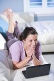 放松使用妇女的长沙发膝上型计算机 免版税库存图片