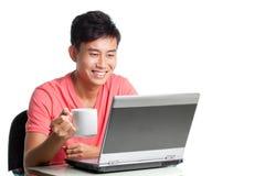 放松使用年轻人的亚洲中国膝上型计&# 免版税库存照片