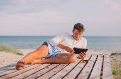 放松使用片剂计算机的商人在海海滩 图库摄影
