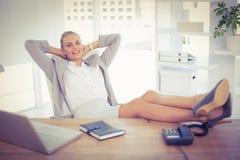 放松使用膝上型计算机的女实业家 免版税库存图片