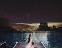 放松假日、一个人脚在床上在游泳池在晚上与城市光和星在天空背景 图库摄影