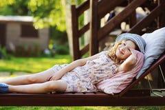 放松儿童的女孩在晴朗的庭院里sunbed,享受夏天 库存图片