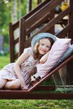 放松儿童的女孩在晴朗的庭院里sunbed,享受暑假 免版税库存照片