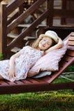 放松儿童的女孩在晴朗的庭院里sunbed,享受暑假 库存照片