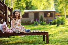 放松儿童的女孩在晴朗的庭院里sunbed 库存图片