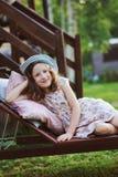 放松儿童的女孩在晴朗的庭院里sunbed 免版税库存图片