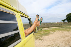 放松凝视的妇女的腿在窗口外面 免版税库存照片