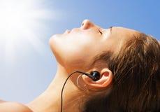 放松可爱的海滩的女孩晒日光浴 免版税图库摄影