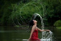 放松和享受使用与水和飞溅的亚裔妇女在热带异乎寻常的河用在bea的绿松石惊人的颜色水 图库摄影