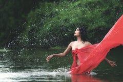 放松和享受使用与水和飞溅的亚裔妇女在热带异乎寻常的河用在bea的绿松石惊人的颜色水 库存照片