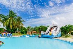 放松和享受他们的时间的观点的与舒适舒适的游泳池的旅馆地面和人 图库摄影