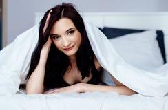 放松和休息在床上的美丽的年轻深色的妇女 免版税库存照片