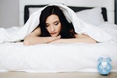 放松和休息在床上的美丽的年轻深色的妇女 免版税图库摄影