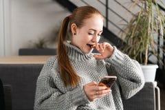 放松和使用一个手机的一个美丽的少年的画象有与朋友的一次交谈,微笑和 库存照片