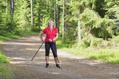 放松和做北欧人走的资深妇女 免版税库存照片