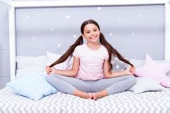放松和凝思 女孩孩子坐床在她的卧室 孩子准备上床 平衡的宜人的时刻 免版税库存照片