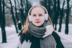 放松和听到与耳机的音乐的女孩 免版税图库摄影