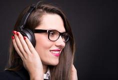 放松和听到音乐的女实业家 免版税库存图片