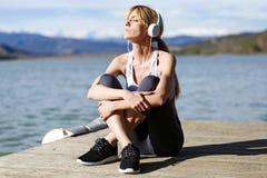 放松和听到音乐的适合和运动的少妇以后在湖旁边解决 免版税库存图片