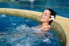 放松和在室外温泉极可意浴缸水池的幸福 免版税库存图片