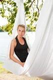放松和实践反地心引力的瑜伽的妇女在树 免版税库存图片