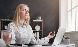放松和思考在工作场所的女实业家 免版税库存图片
