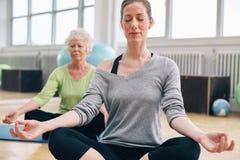 放松和思考在他们的瑜伽类的妇女在健身房 免版税库存照片