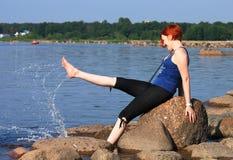 放松和飞溅水的海滩的愉快的女孩 免版税库存照片