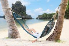 放松和说谎在海滩的一个吊床的游人女孩 免版税库存照片