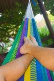 放松在一个五颜六色的吊床在一个热带庭院里 库存照片