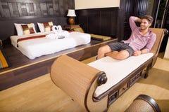 放松在一个亚洲被称呼的旅馆客房的年轻人 免版税图库摄影